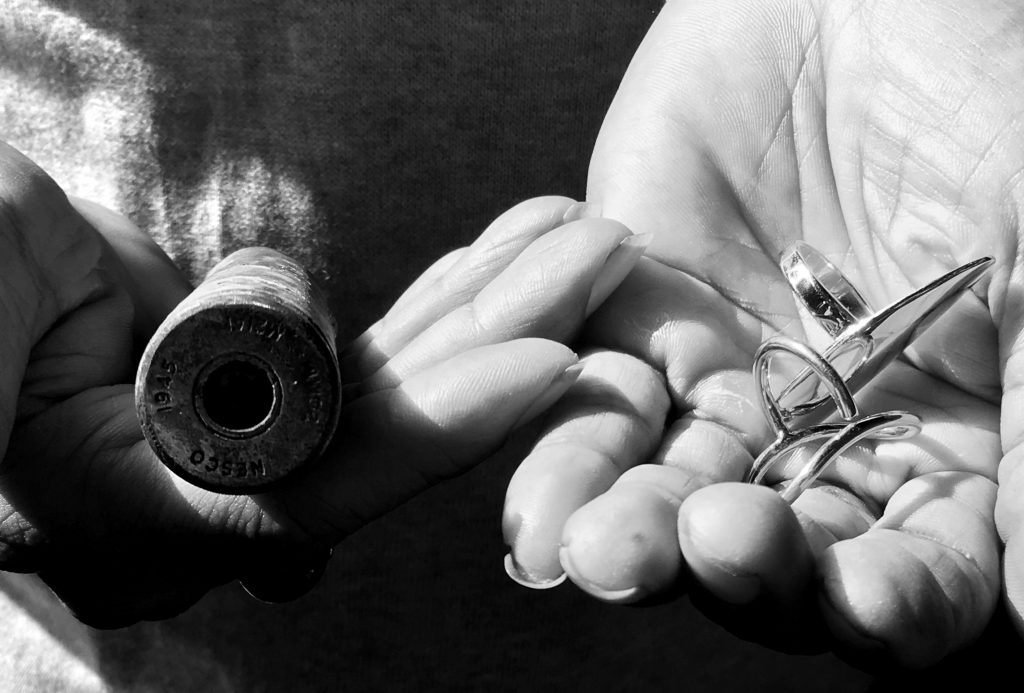 hand holding jewellery and bullet